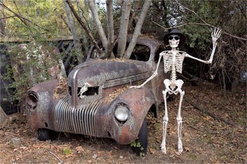 a skeleton posed next to an old car