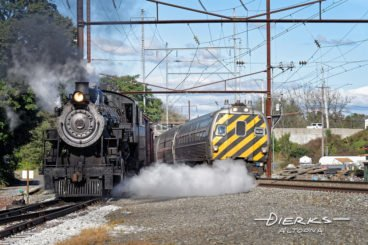 Modern Amtrak train and the Strasburg Railroad steam locomotive meet at the junction