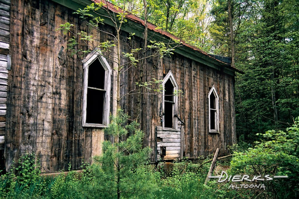 Abandoned Victorian church in deep woods.