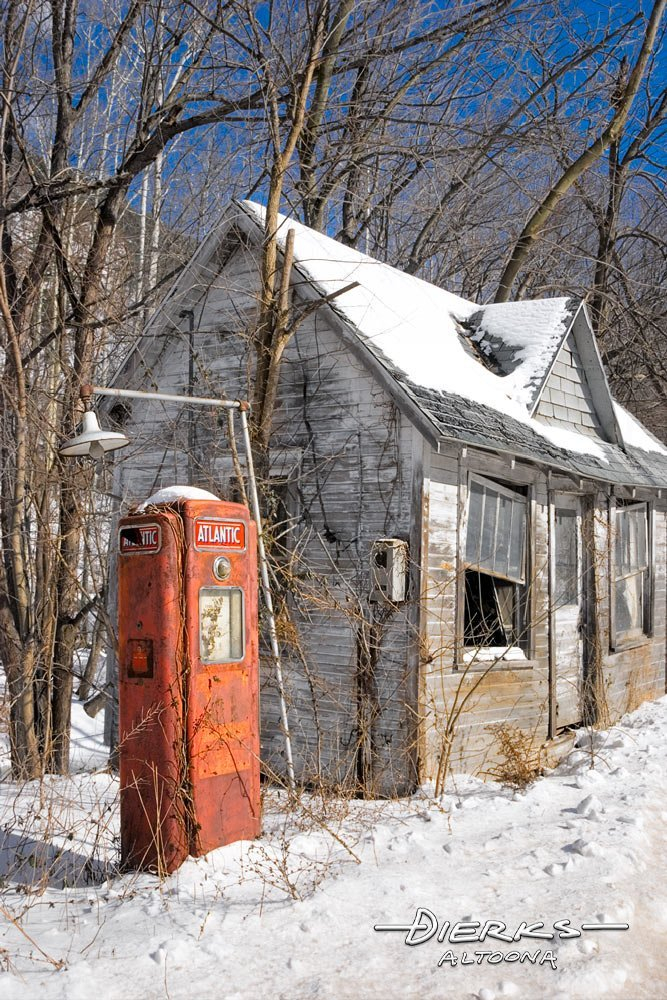 An old gas station with red Atlantic gas pump in winter snow in the Pennsylvania outback country.