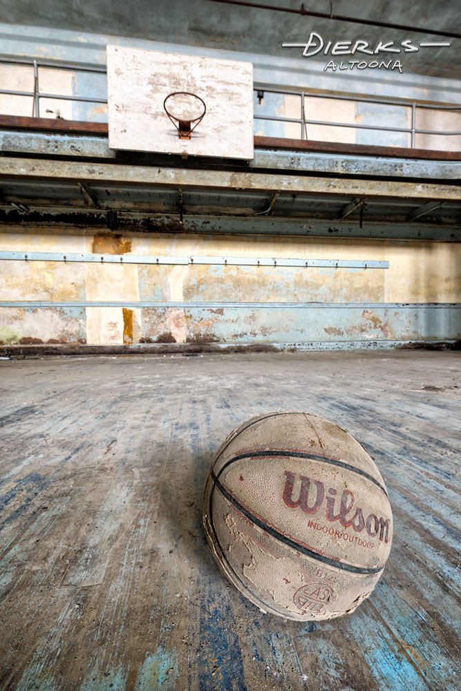 Basketball laying in abandoned school gym.