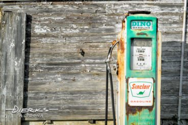 Weathered green Sinclair gas pump beside a farm shed with Dino.