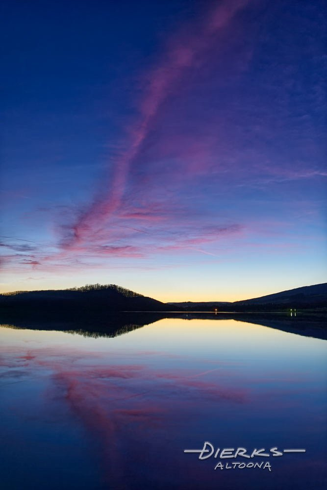 Dramatic sunset in pink and blue above the water of an evening lake.