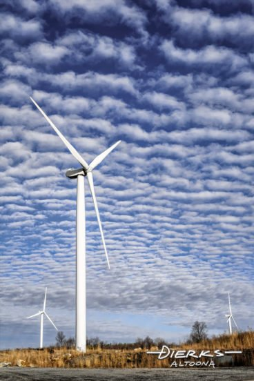 Wind turbines standing tall against a baske weave sky in Pennsylvania.