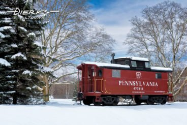 Pennsylvania Railroad PRR caboose on display in winter snow in Tyrone, PA.