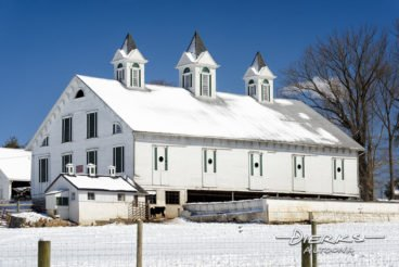 A fancy white barn in snow and sun, Victorian architecture with fancy cupolas.