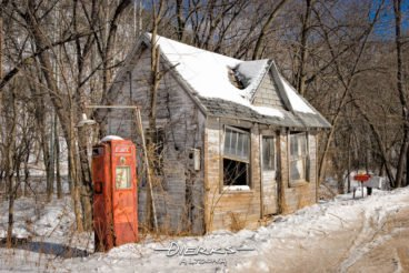 Abandoned gas station in the country in winter snow with Atlantic gas pump, rural America out in the countryside.