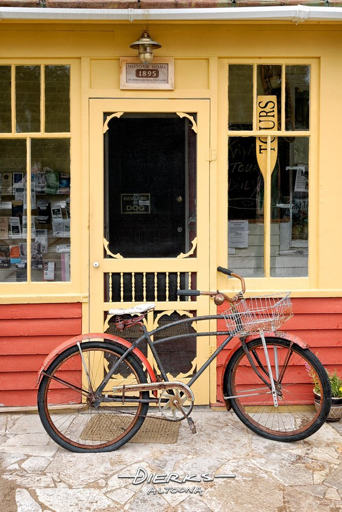 An old red bicycle in front of a yellow wooden screen door of an old fashioned store selling penny candy.