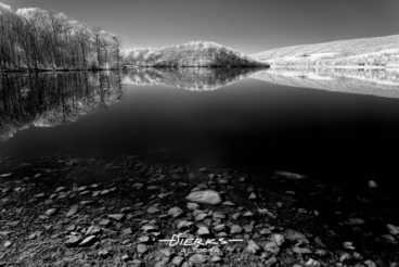 Shore stones fading away into deeper dark water, black and white infrared photography.