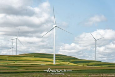 Wind turbines producing green alternative energy while turning in the breezes high above the rolling farmland of central Pennsylvania.