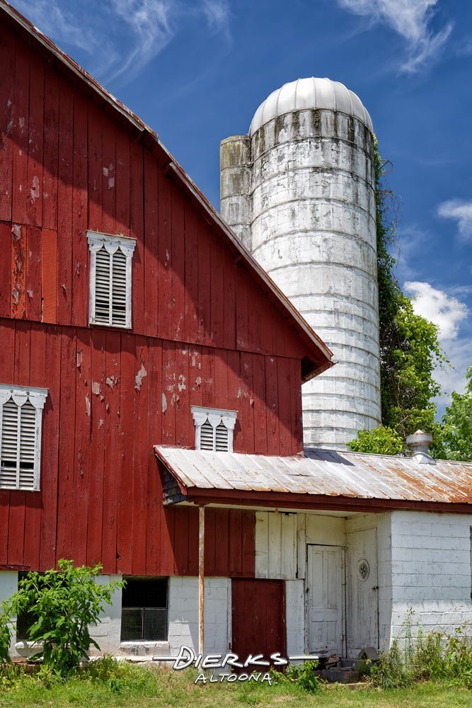 A red and white dairy barn with milk house under blue summer sky.