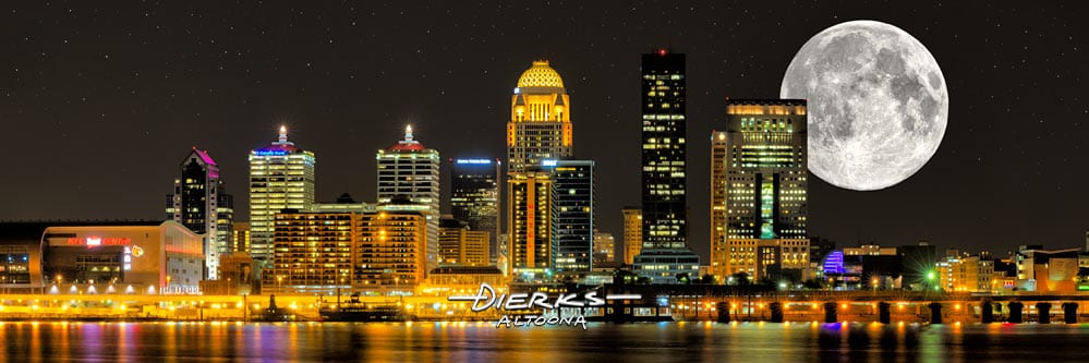 City view of night skyline of Louisville Kentucky along the Ohio River with a full moon close by.