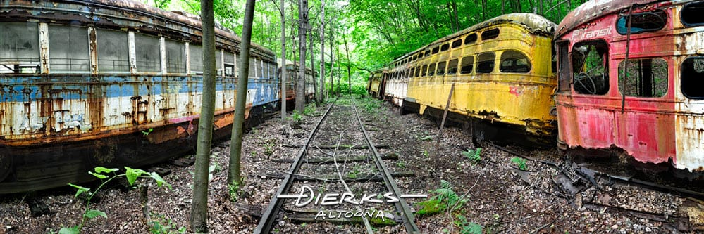 A trolley graveyard in the woods full of old rusting streetcars including PAT Transit from Pittsburgh.