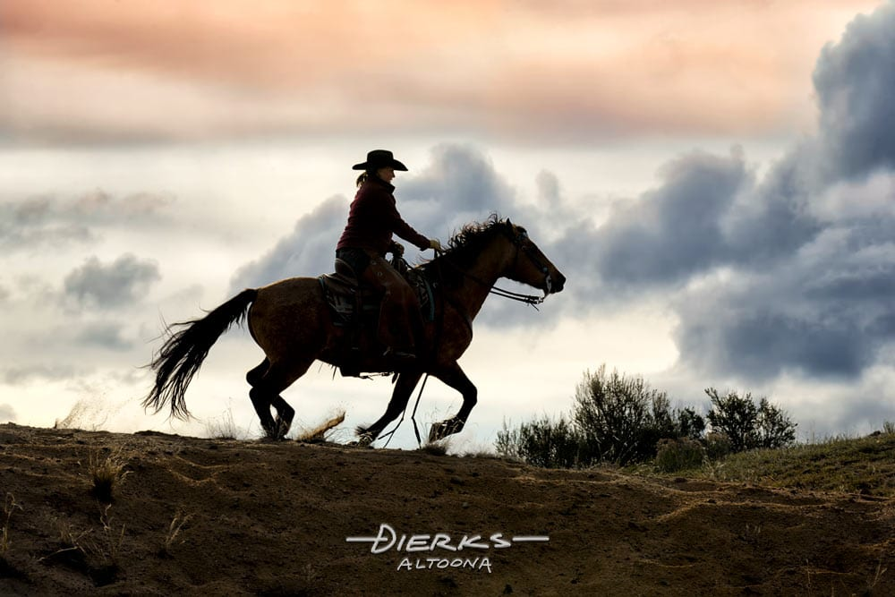 Horse and rider moving across a sandy ridgeline at a gallop as the cold evening sun goes down in Colorado.