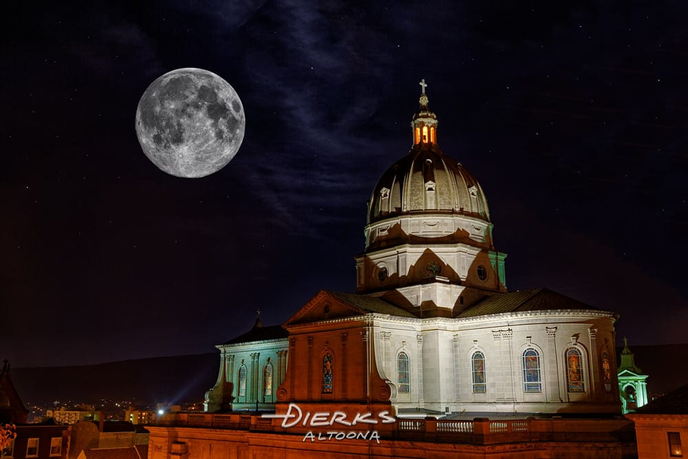The Altoona Cathedral at night under a full moon with the artificial lighting showing in different colors.