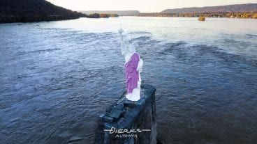 The 25 foot miniature Statue Of Liberty in the Susquehanna River at Dauphin PA, with her robe painted for breast cancer awareness.