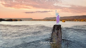 The miniature Statue Of Liberty in the Susquehanna River at Dauphin PA in an upriver sunset view, with her robe painted for breast cancer awareness. It lies jut north of Harrisburg, PA.