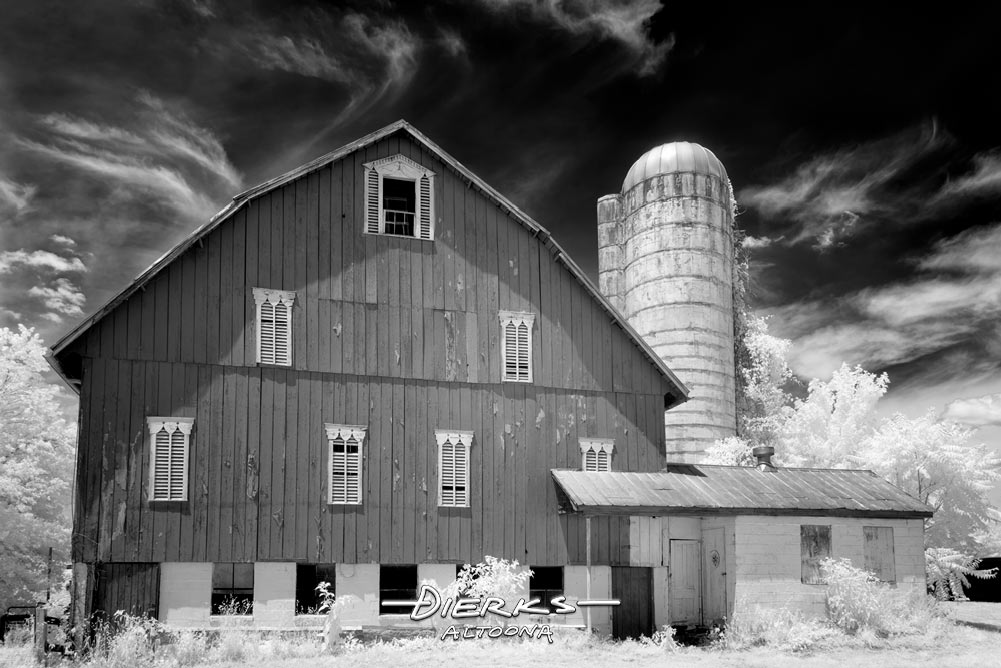 A retired dairy barn in black and white under a sky of swirling clouds.