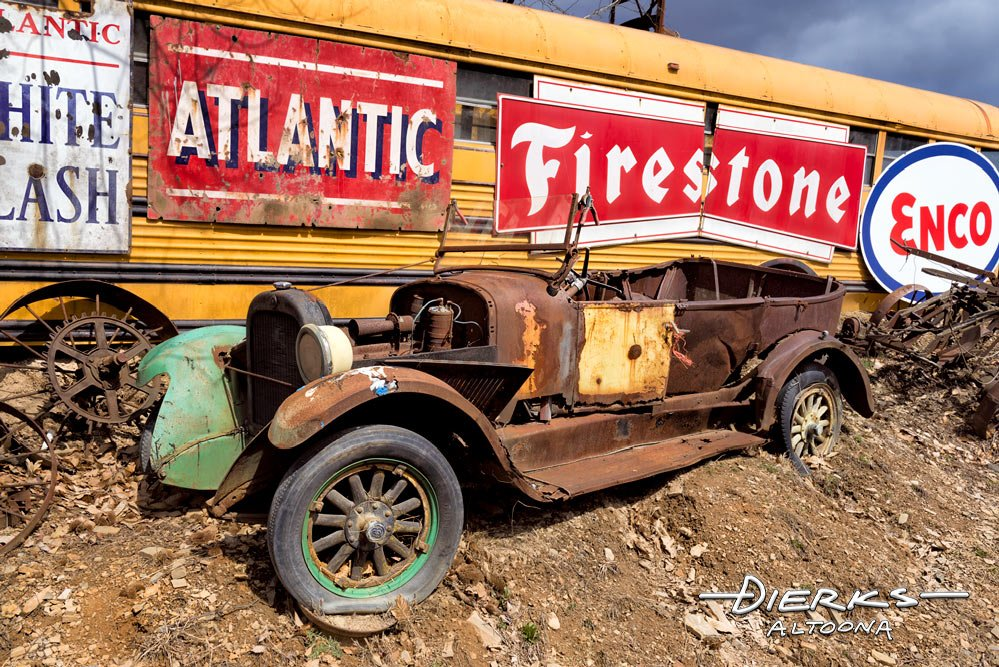 A very vintage junkyard car on top of a dirt pile from the real jalopy days.