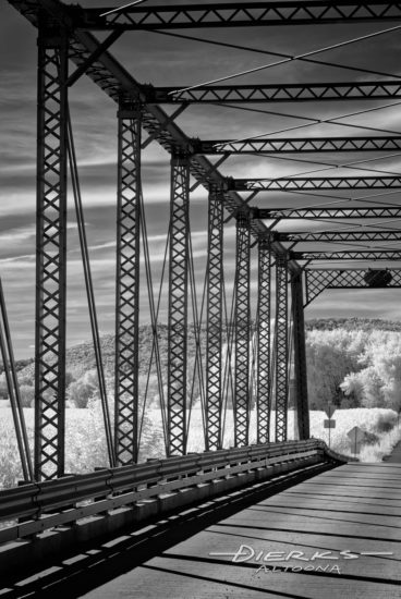 A black and white view to a summer country landscape through an old single-lane truss bridge from 1889.