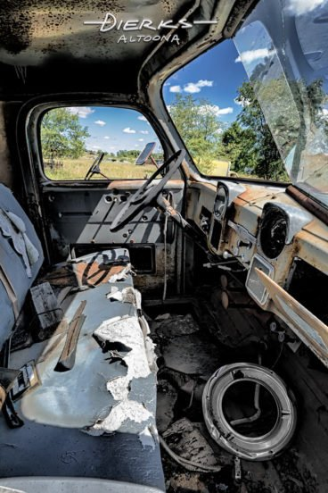 The trashed and rough interior of a 1952 Dodge pickup truck cab in a summer junkyard.