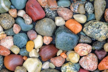 Wet colorful river rocks of granite and sandstone in close up.