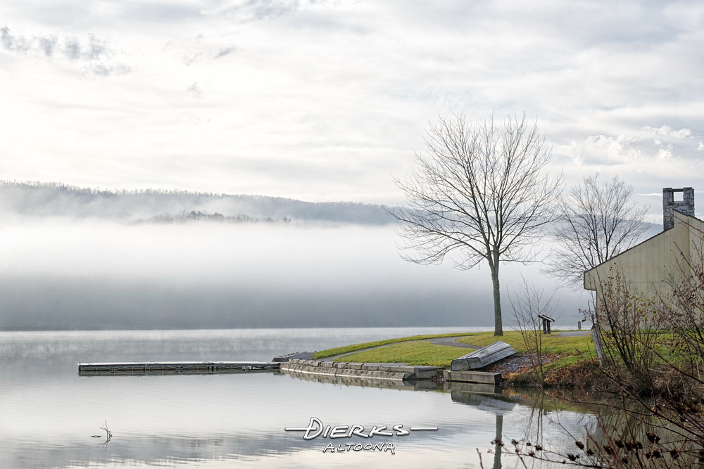 Morning fog masks the mountains behind this summer lake in Pennsylvania.
