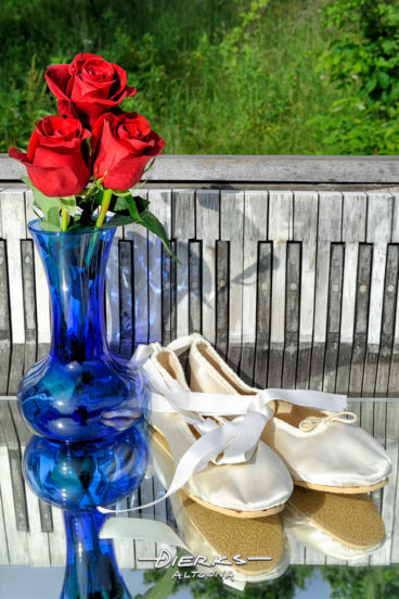 Ballet slippers and red roses with a piano keyboard outside in nature.