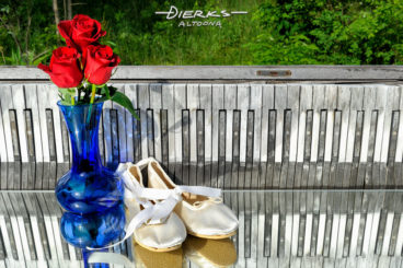 Ballet slippers and red roses in a blue vase outside with a weathered piano keyboard.