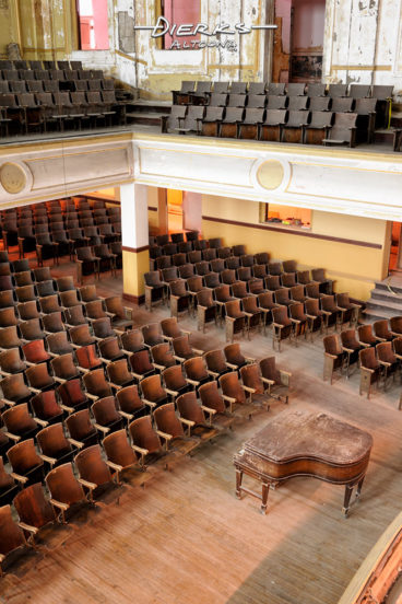 Empty and abandoned old high school auditorium with a grand piano as seen from balcony.