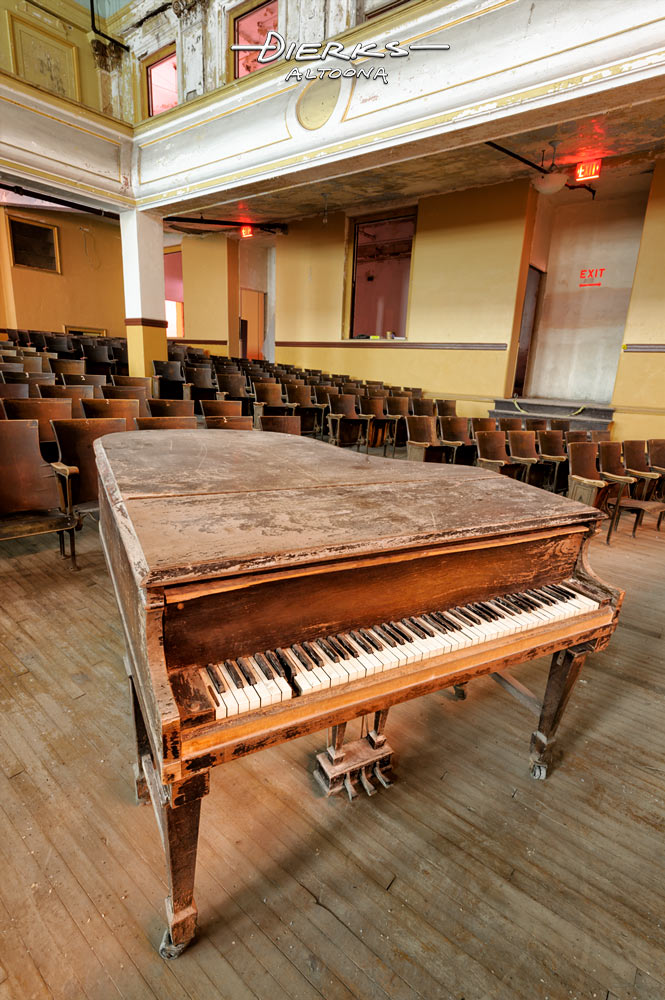 Empty and abandoned high school auditorium with weathered and worn grand piano missing a key in the keyboard.