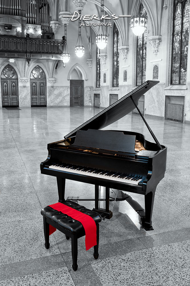 An elegant black grand piano with the lid up sits in a Gothic Revival church hall.
