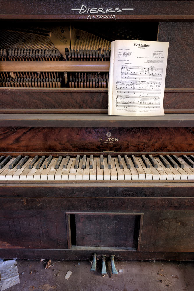 Worn and broken abandoned upright piano with battered keyboard and old sheet music by Jobim.