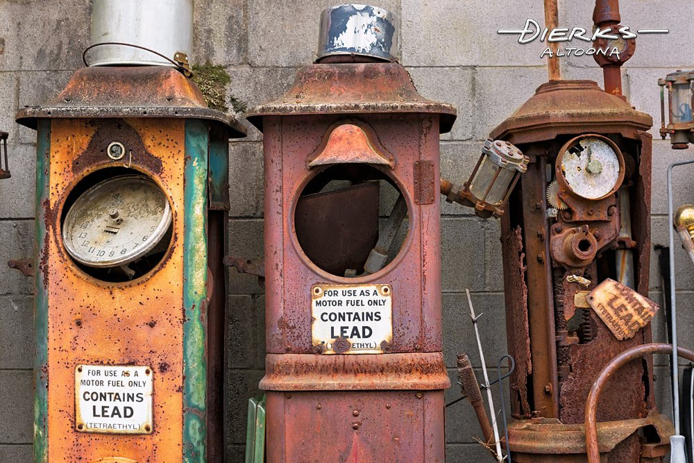 Three rusty antique gas pumps with dial faces from the 1920s or 1930s.