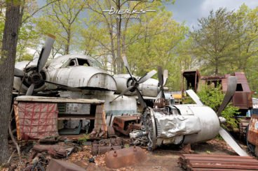 View of an airplane graveyard and metal yard in the Spring woods, featuring an old military cargo plane.