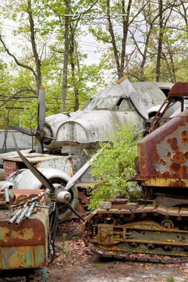 Airplane nose and engine and other scrap metal in a wooded junkyard.