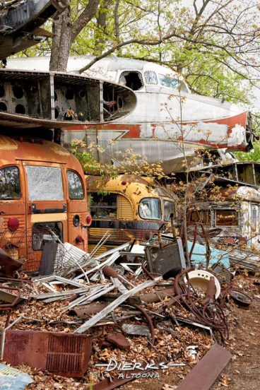 An airplane nose sits stacked on old buses and other junk in a wooded junkyard.
