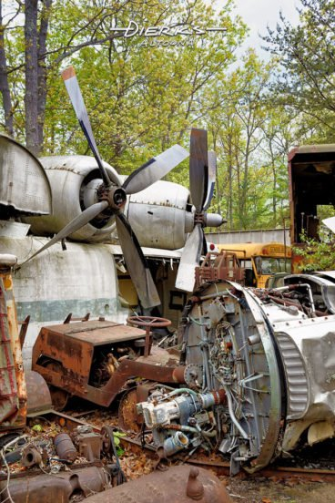 Airplane engines and propellers along with other metal scrap in a wooded junkyard.