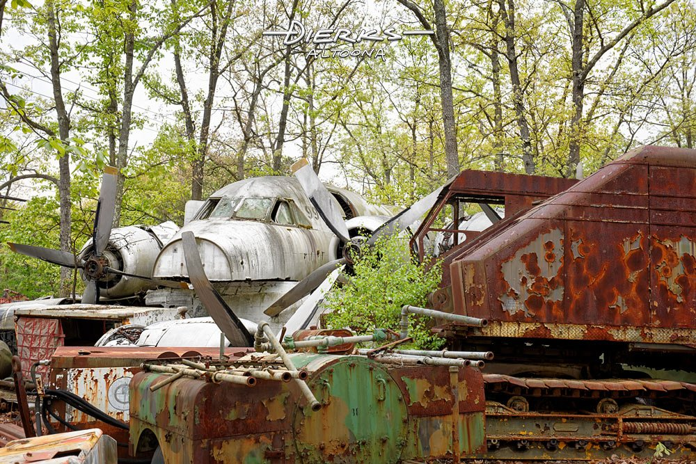 An airplane fuselage and engines with propellers in the middle of other metal junk and scrap in wooded junkyard.