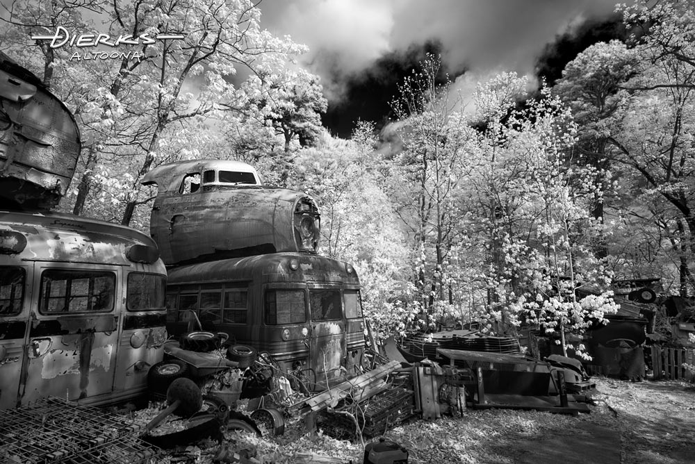 A wooded junkyard in the outback with an airplane cockpit stacked on a school bus. A black and white infrared picture.