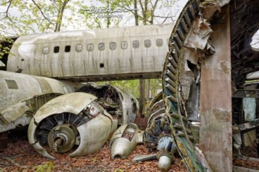 Airplane fuselages and and a crumpled engine lying in a wooded scrap metal yard.