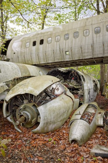 Airplane fuselage parts cut up and stacked in a wooded junkyard with a cracked open engine laying in the foreground.