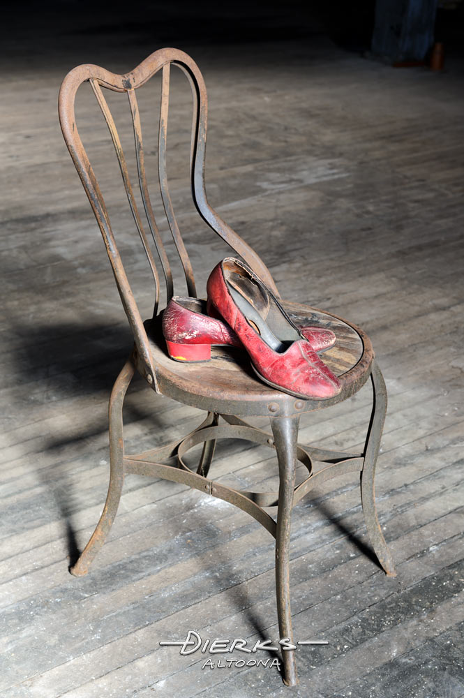 Old red shoes on a rusty metal chair left after the last dance, with a dirty wooden factory floor for a background.