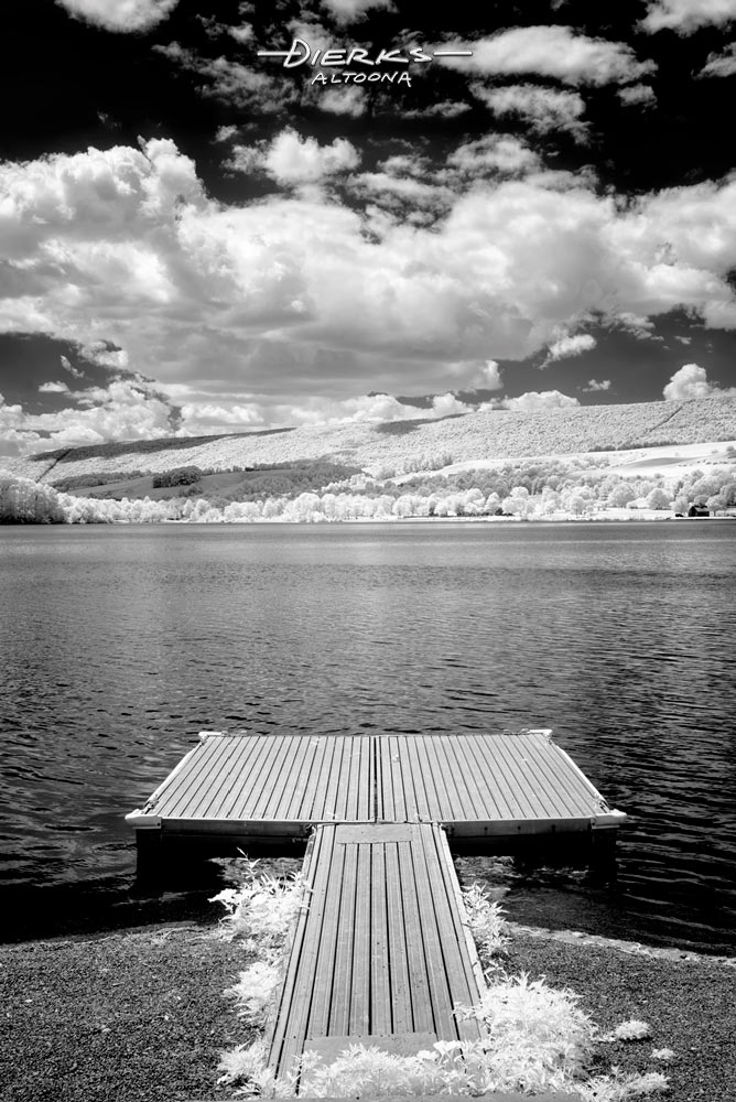 At a summer park, a lake dock under low fluffy white clouds above the water.