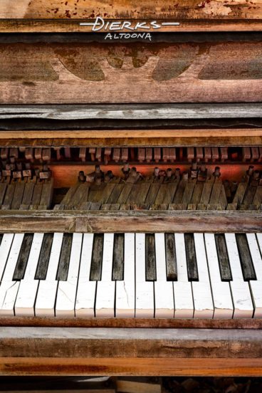 An abandoned piano sitting outside is ruined and wrecked from exposure to the weather, with broken off black keys and chipped keyboard.
