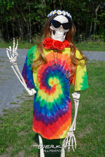 A skeleton flower child in a tie dye shirt throws the peace sign, a true throwback hippie chic.