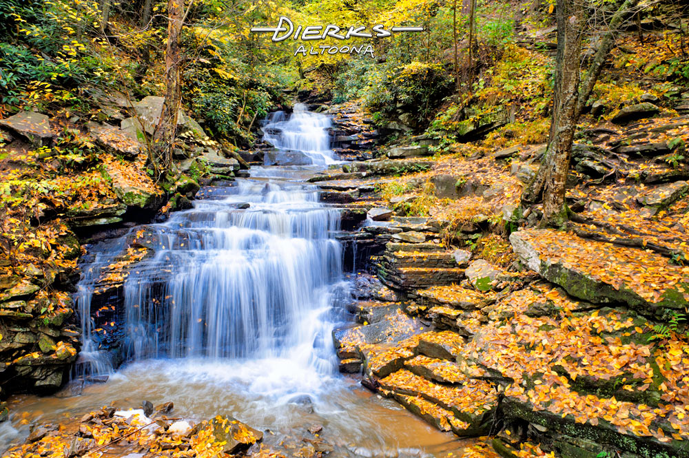 A waterfall in golden leaves of the forested Fall scenery at Rainbow Falls in Trough Creek State Park in Pennsylvania.