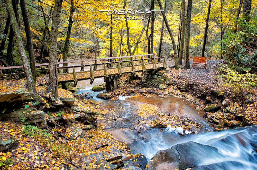 A mountain stream goes over a rocky waterfall and under a bridge in the scenic Fall woods at Trough Creek State Park in Pennsylvania.