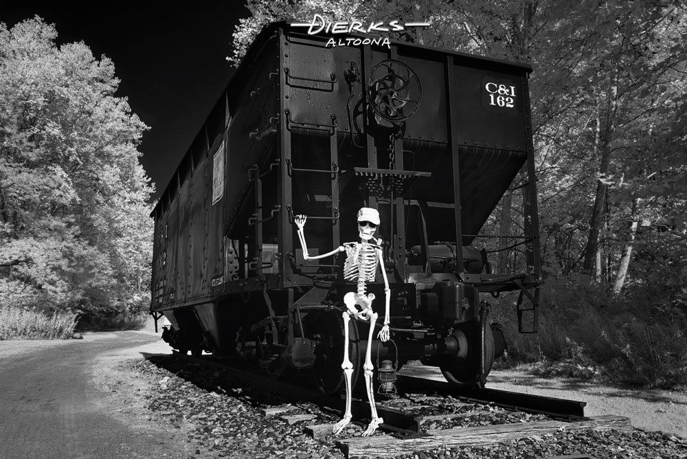 A skeleton railroader with a lantern is working the afternoon freight train on the Great Divide & Nevermore Railroad.