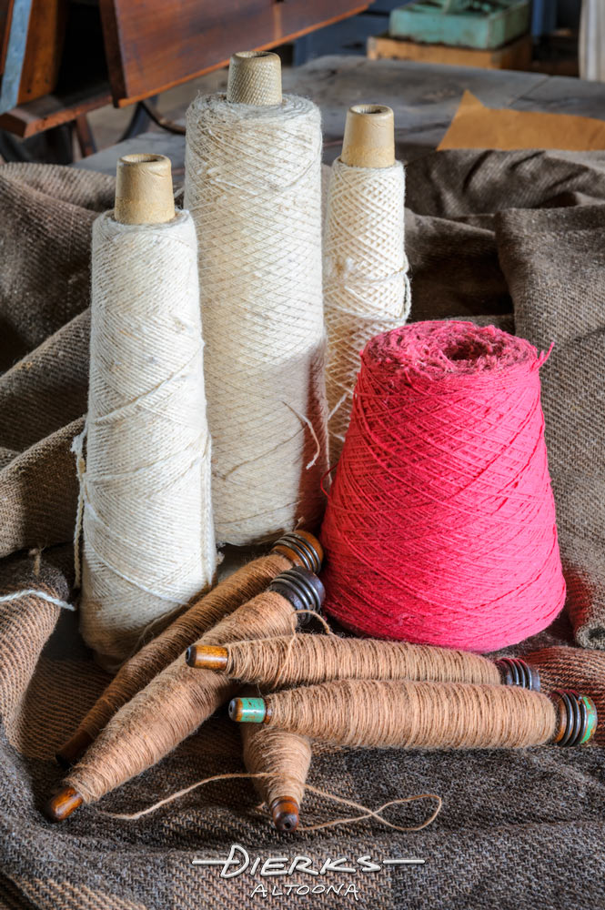 In the old fashioned blanket mill, new yarn on bobbins gets wrapped onto quills that fit the weaving machine.